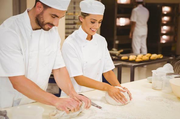 2 jeunes boulangers en train de préparer du pain