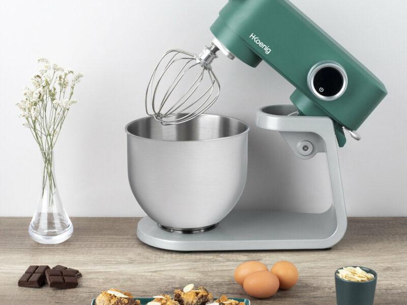 Un robot pâtissier sur un plan de travail avec du chocolat, des oeufs et du cake à côté